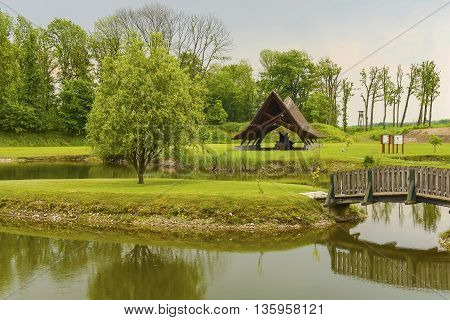A small traditional cottage covered with straw at a lake beautiful reflection of clouds in the water at the far shore people are fishing (face not recognizable)