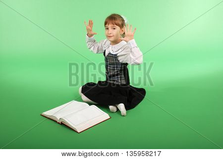 Girl in a school uniform sitting in front of an open book and shows ten fingers isolated on green