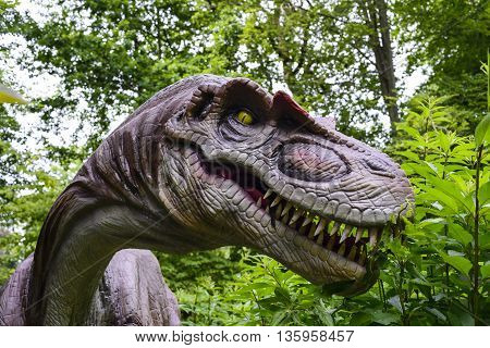 A dinosaur statue in a recreation park greenery in background