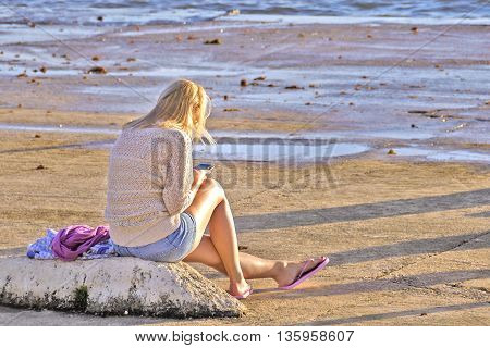 A young blonde girl on the beach enjoying the sunset and exchanging short messages on mobile phone facing away from viewer