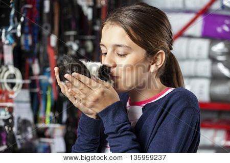 Girl Kissing Guinea Pig At Pet Store