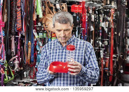 Customer Examining Pet Food Bowl At Store