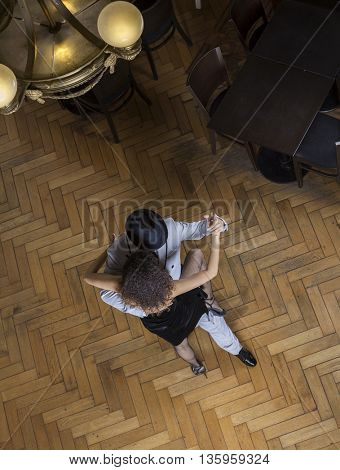 Man And Woman Performing Tango On Wooden Floor