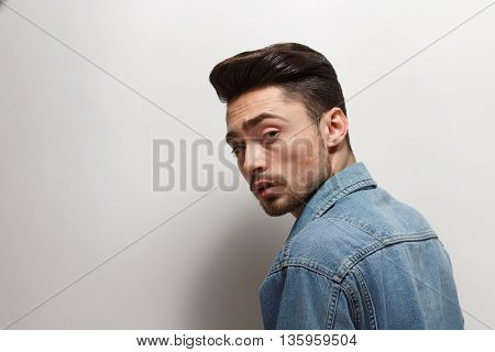 Portrait of handsome young man with bright black hair over white background. Male model in jeans shirt with modern hairstyle in studio.