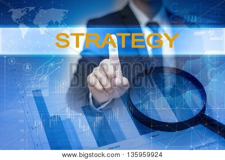 Businessman hand touching STRATEGY button on virtual screen