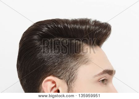 Top view profile of young handsome man's hair over white background. Model male with modern hairstyle posing for fashion magazine in studio.