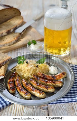Bavarian beer garden meal - Fried sausages from Nuremberg with sauerkraut and horseradish traditionally served on a pewter plate with hearty farmhouse bread and a tankard of cold Munich lager beer