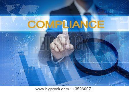 Businessman hand touching COMPLIANCE button on virtual screen