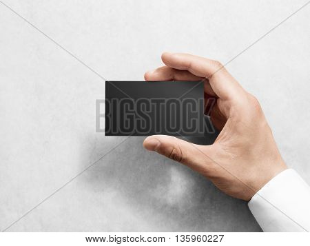 Hand holding blank plain black business card design mockup. Clear calling card mock up template hold arm. Visit pasteboard paper surface display front. Check small offset card print dark business card