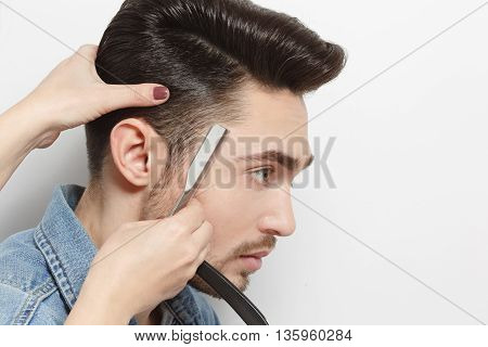 Portrait of handsome young man with black hair having haircut with blade by hairdresser over white background in studio.
