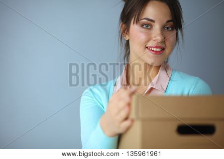 Portrait of pretty woman holding a box .