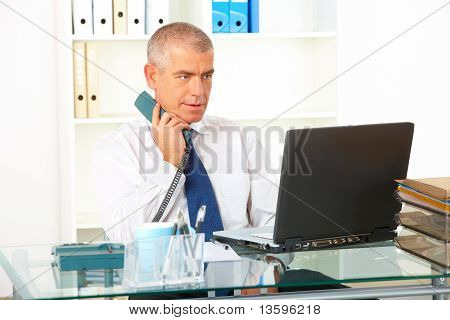 Businessman With Landline Phone Looking At Laptop