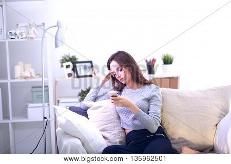 Pretty girl using her smartphone on couch at home in the living room.