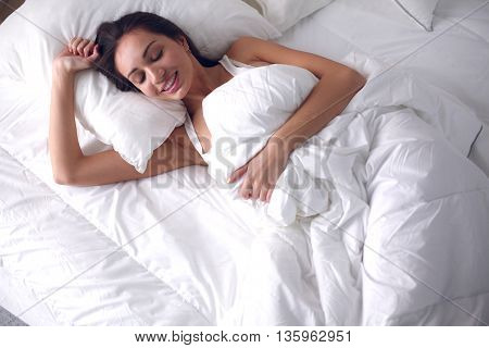 Pretty woman lying in bed at home .