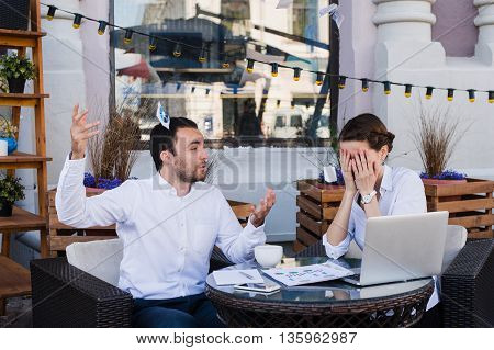 Businessmen shocked at colleague screaming and throwing papers in the air at outdoors cafe during lunch break.