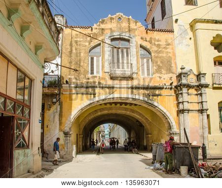 HAVANA - CUBA JUNE 19, 2016: People walk under the Arch of Belen (Arco de Belén) over Acosta street which is part of the historic Belen Convent (Convento de Nuestra Señora de Belén) established by the Religious Order of the Jesuits in 1767.