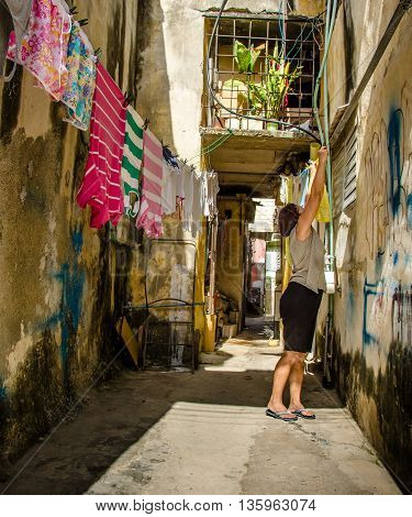 HAVANA - CUBA JUNE 19, 2016: A woman hangs up laundry outside of her home in the historic neighbourhood of La Habana Vieja.