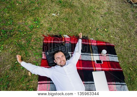 Image of businessman relaxing on the grass with laptop near by.