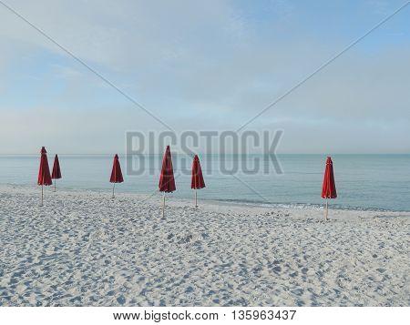 Six Red Umbrellas on White Sand Beach