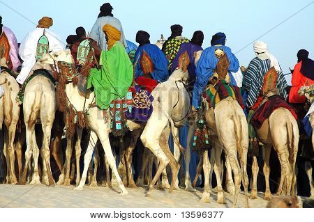Man Riding Behind A Group Of Tuareg On Camels