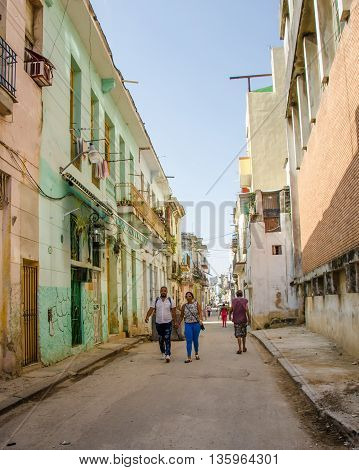 HAVANA - CUBA JUNE 19, 2016: Couple walks along a narrow street of deteriorating homes in the La Habana Vieja neighborhood.