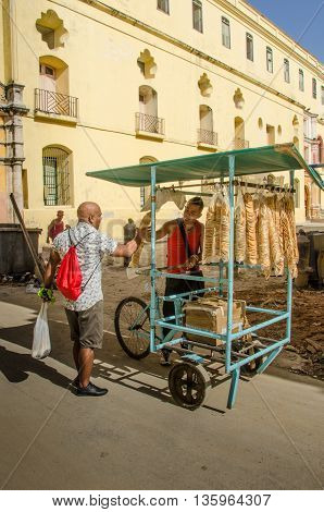 HAVANA - CUBA JUNE 19, 2016: Man sells biscuits from his bicycle to a male customer in the historic La Habana Vieja neighborhood.