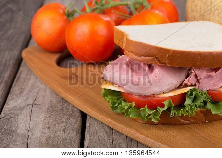 Roast beef sandwich closeup with tomato lettuce and cheese
