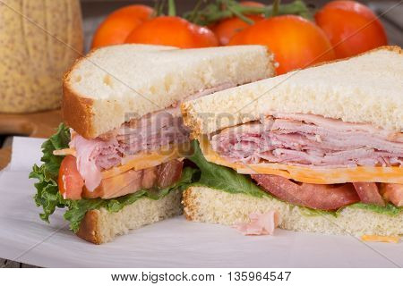 Closeup of a ham sandwich with cheese lettuce and tomato