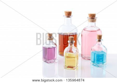 Aromatic essential oils in old bottles different colors isolated on white with reflection