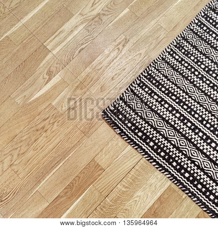Stylish black and white rug with ethnic design on hardwood floor.