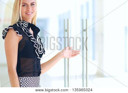 A beautiful blond business woman open the office door
