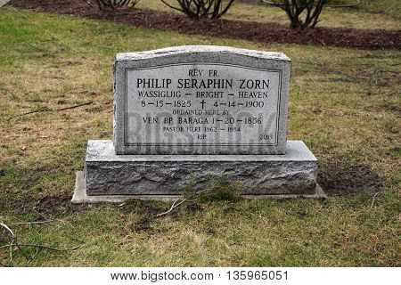 HARBOR SPRINGS, MICHIGAN / UNITED STATES - DECEMBER 24, 2015: A memorial to Reverend Father Philip Seraphin Zorn, who served as pastor of the Holy Childhood of Jesus Church from 1862 to 1884, stands outside the church in Harbor Springs.