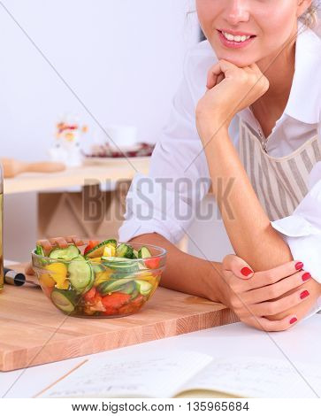 Smiling young woman preparing salad in the kitchen .