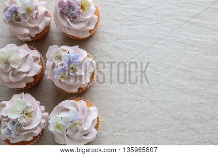 Purple Cupcakes With Sugared Edible Flowers Copy Space Background.