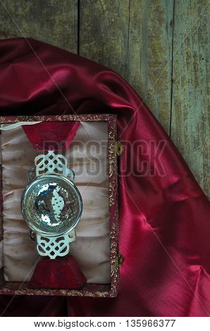 Antique Silver Tea Strainer on Red Silk and Wooden Board