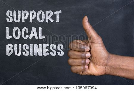 Male hand giving the thumbs up gesture to the phrase Support Local Business written on a blackboard