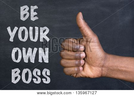 Male hand giving the thumbs up gesture to the phrase Be Your Own Boss written on a blackboard