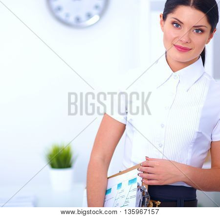 Portrait of a young woman standing with folder .