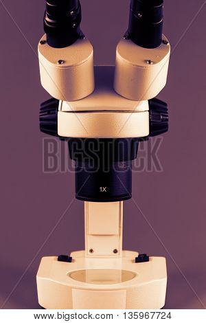 Incident binocular research microscope on gray background