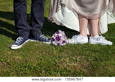 Men feet in blue sneakers, and female legs in white sneakers with rhinestones on a green lawn. Wedding bouquet of white and purple lace
