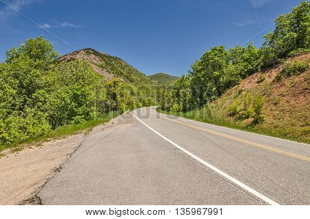 Two-lane road with a big curve as it winds through mountains with vibrant green trees and blue skies