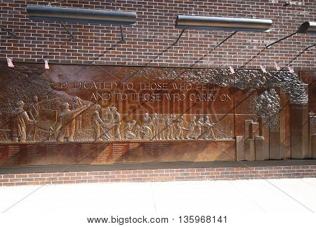NEW YORK - MARCH 6, 2016: FDNY Memorial Wall, a 56 foot bronze bas-relief Sculpture, at FDNY Engine 10 and Ladder 10 Firehouse across from World Trade Center site and the 9/11 Memorial in Manhattan.