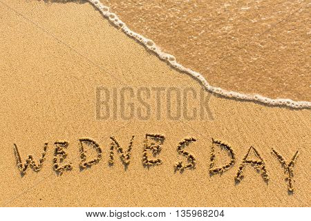 Wednesday - inscription on sand beach with the soft wave.