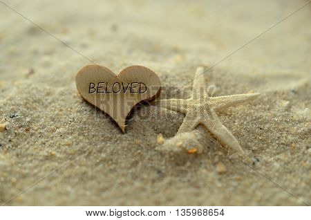 Depth of field beloved text carved/engraved in heart shape piece of wood on sand beach with starfish