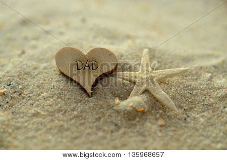 Depth of field dad text carved/engraved in heart shape piece of wood on sand beach with starfish