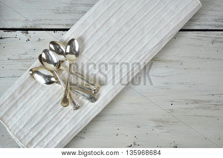Antique Silver Teaspoons on White Rustic Board and Fabric