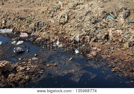 BALI INDONESIA - APRIL 30: Plastic household garbage and poisonous industrial waste contaminates soil land and water at a polluted landfill site on April 30 2016 in Suwung Bali Indonesia.