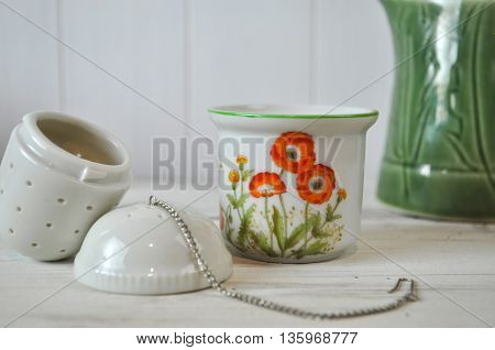 Ceramic Tea Strainer with Flower Decorated Container on White Rustic Board