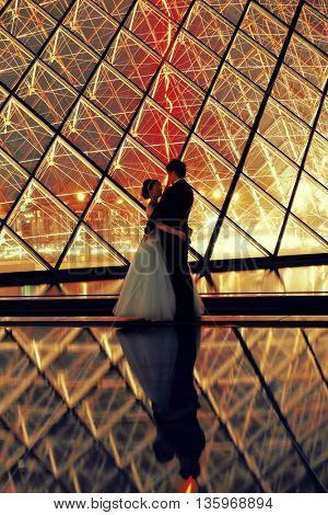 PARIS, FRANCE - MAY 13: A lover couple in front of Louvreon May 13, 2015 in Paris. With over 60k sqM of exhibition space, Louvre is the biggest Museum in Paris.