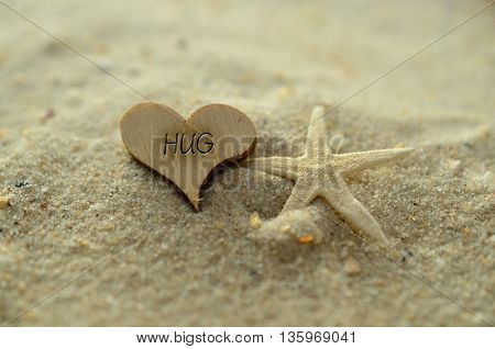Depth of field hug text carved/engraved in heart shape piece of wood on sand beach with starfish